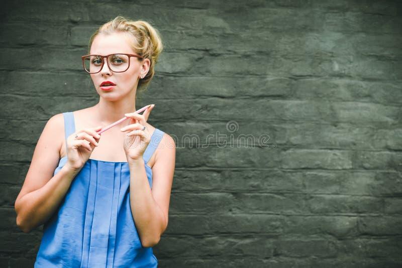 Ухищренный усмехаясь белокурый красивый женский держа карандаш на серой предпосылке стены стоковая фотография rf