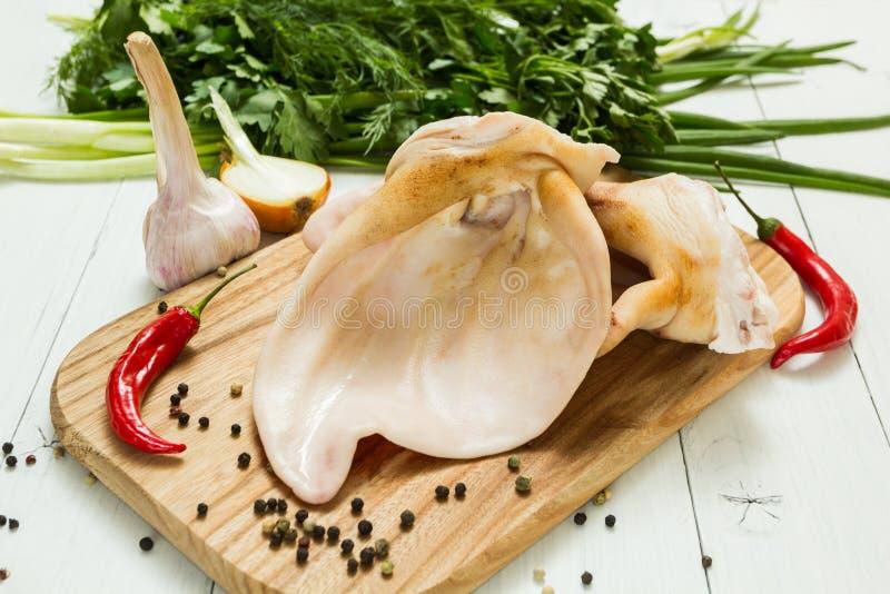 Ухо свиньи на разделочной доске с овощами, деликатесе стоковое фото