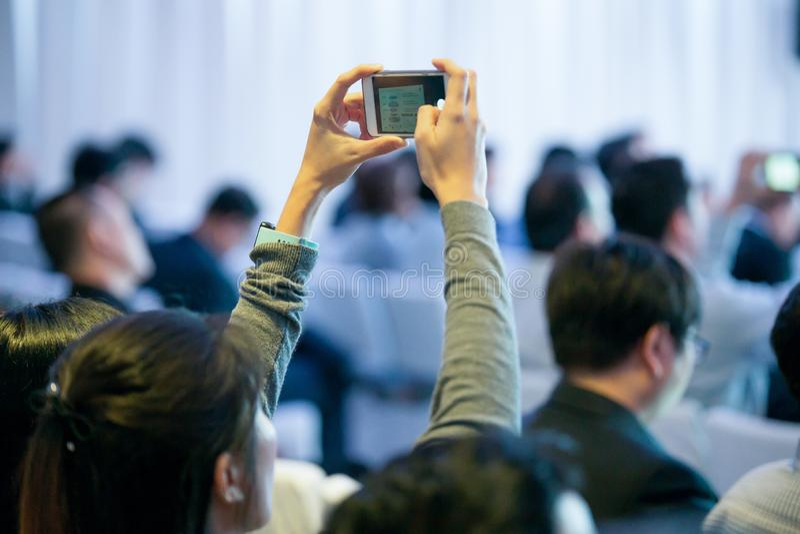 Участники используют фотографию смартфона в конференц-зале стоковые изображения rf