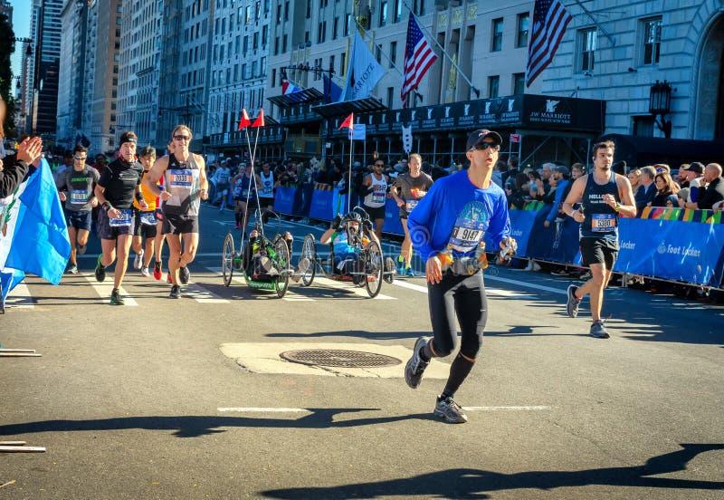 Участники разделения кресло-коляскы во время марафона Нью-Йорка стоковое фото