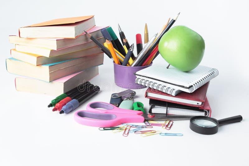 Учебники и разнообразие школьные принадлежности на белой предпосылке яблоко записывает красный цвет образования принципиальной сх стоковые фотографии rf
