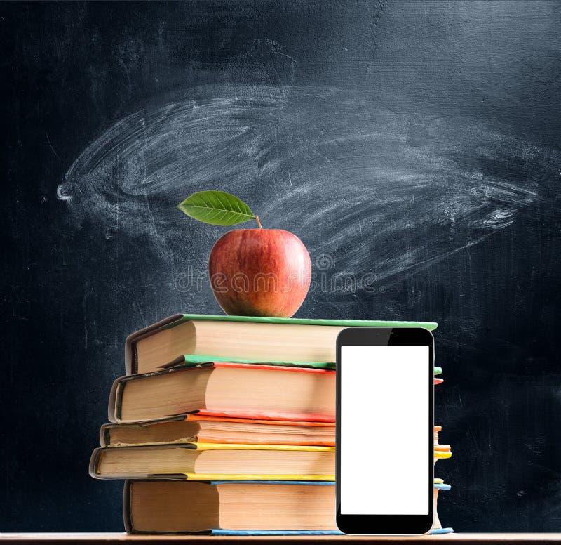 Учебники и smartphone стоковое изображение