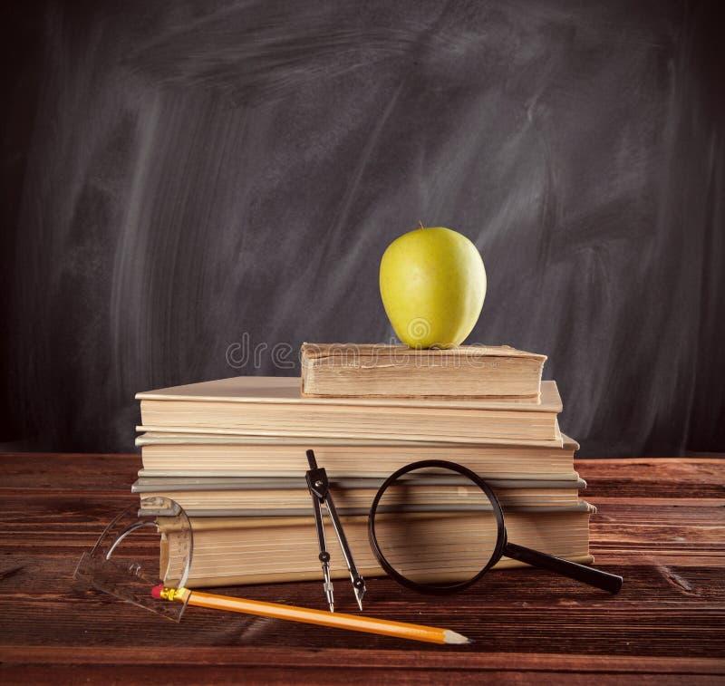 Учебники при аксессуары помещенные на деревянном стоковое фото