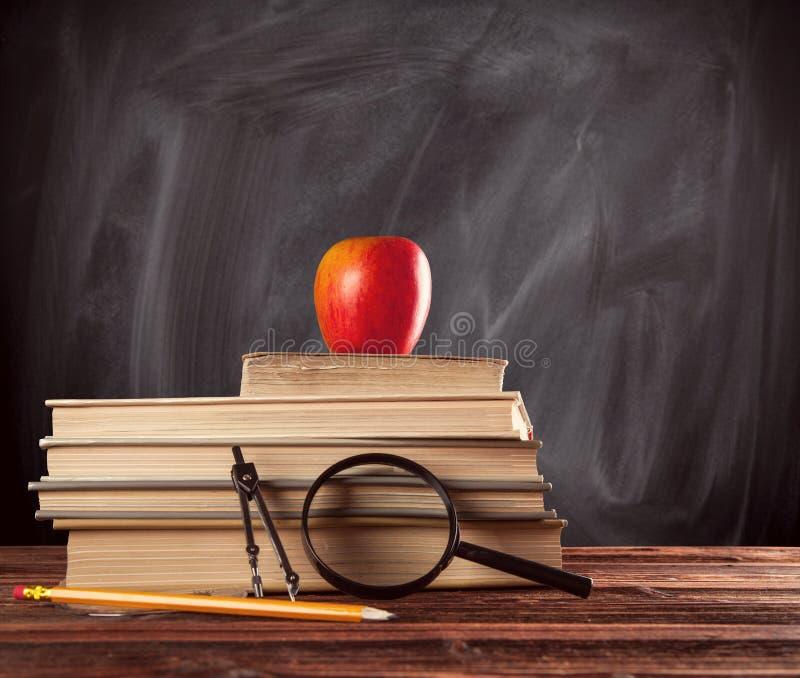Учебники при аксессуары помещенные на деревянном стоковое изображение