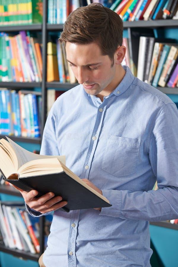 Учебник чтения студента университета в библиотеке стоковое изображение