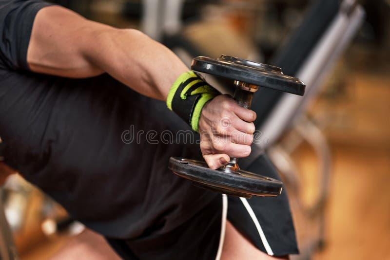 Учебное упражнени веса для строя концепции мышцы, близкое вверх по руке молодого человека делает тренировку в трицепсе гантели стоковое фото rf