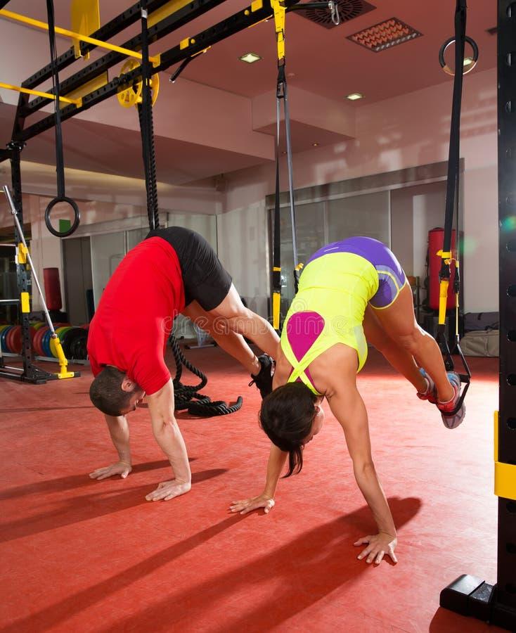 Учебные упражнени пригодности TRX на женщине и человеке спортзала стоковые фото