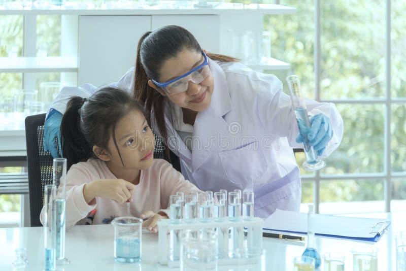 Ученые объясняют эксперименты путем просматривать микроскоп в лаборатории ученые работая в лаборатории стоковое фото rf