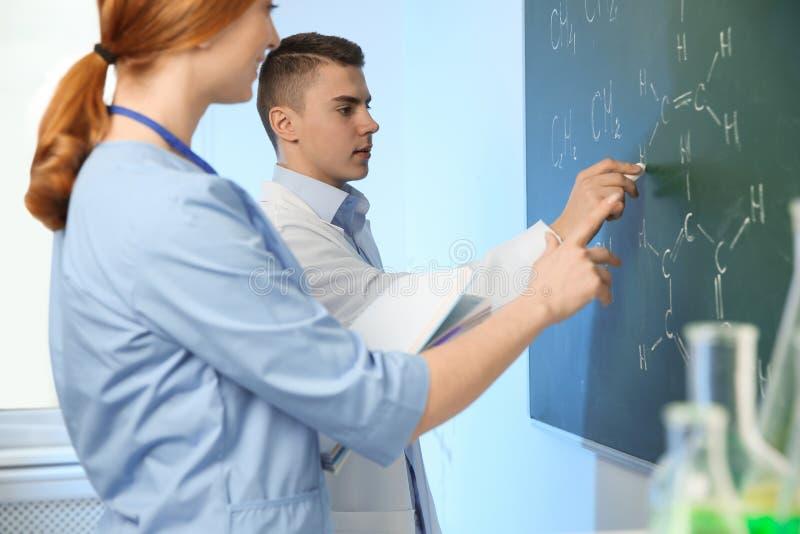 Ученые писать химические формулы на доске стоковые фотографии rf