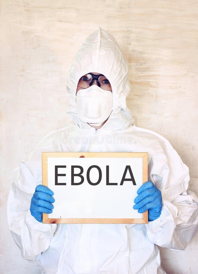 Ученый лаборатории в костюме безопасности держа доску с ebola слова стоковое изображение rf