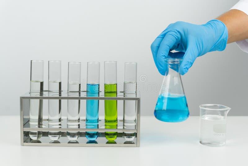 Ученый держа голубую жидкостную склянку стоковые фото