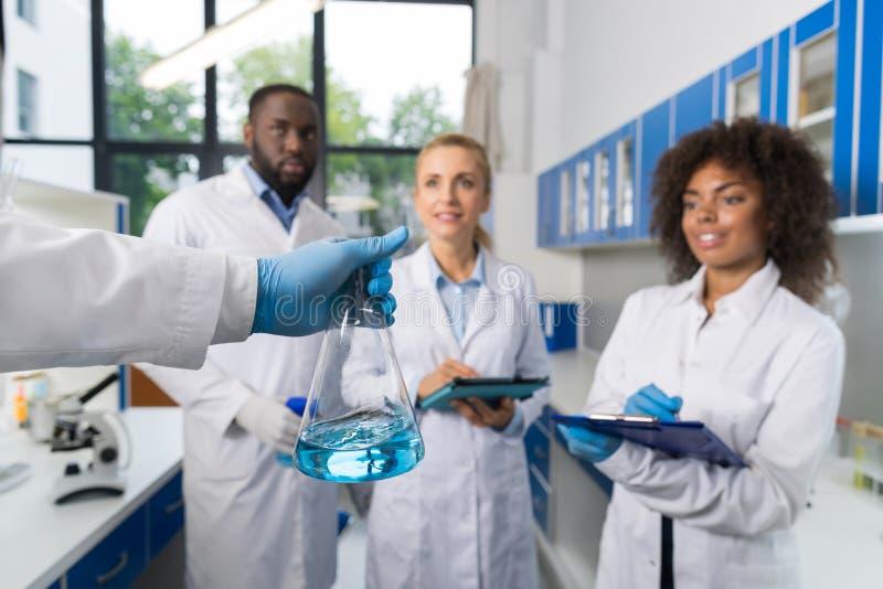 Ученый держа склянку с группой в составе студенты принимая примечания делая исследование в лаборатории, команде гонки смешивания  стоковая фотография