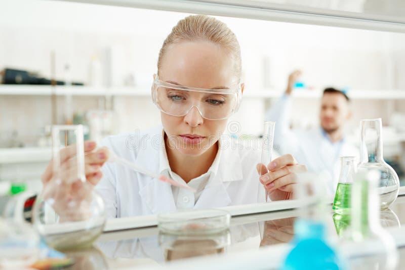 Ученый женщины выполняя эксперимент в лаборатории стоковое изображение rf