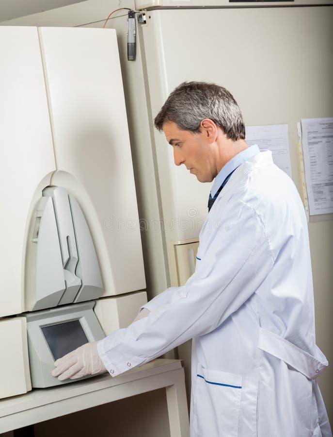 Ученый используя аппаратуру культуры крови в лаборатории стоковая фотография rf