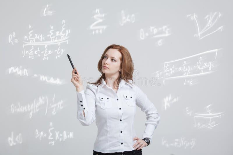 Ученый или студент женщины при ручка работая с различными математиками средней школы и формулой науки стоковое фото