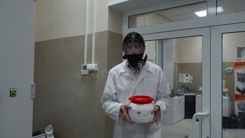 Ученый нося защитный костюм и нося опарник токсической жидкости внутри зоны biohazard стоковые фотографии rf