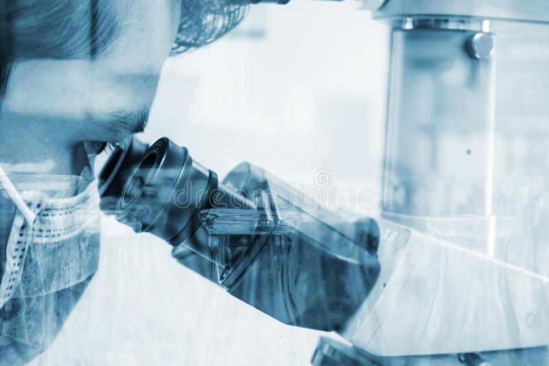 Ученый смотря через микроскоп для образцов испытания химии стоковые фото