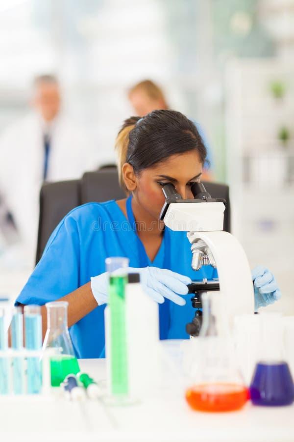 Ученый смотря через микроскоп стоковое фото rf