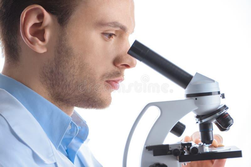 Ученый человека смотря через микроскоп на белизне стоковое фото rf