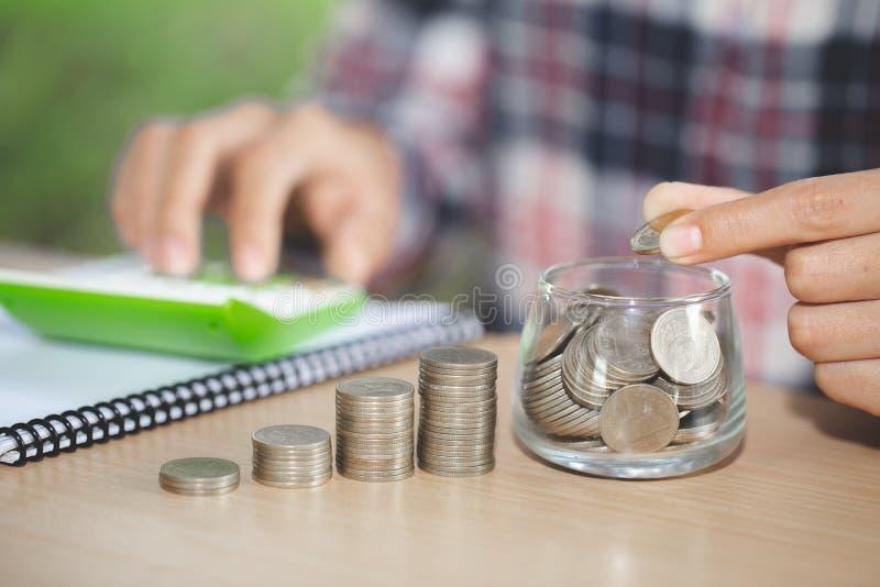 Учет коммерческих операций с деньгами сбережений с рукой кладя монетки в стекло кувшина, бизнесмена писать финансовый учет, конце стоковое изображение rf