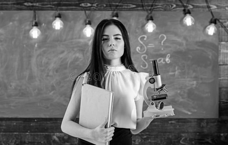 Учитель биологии держит книгу и микроскоп Дама в официально носке на спокойной стороне в классе Ученый дамы держит книгу стоковое изображение