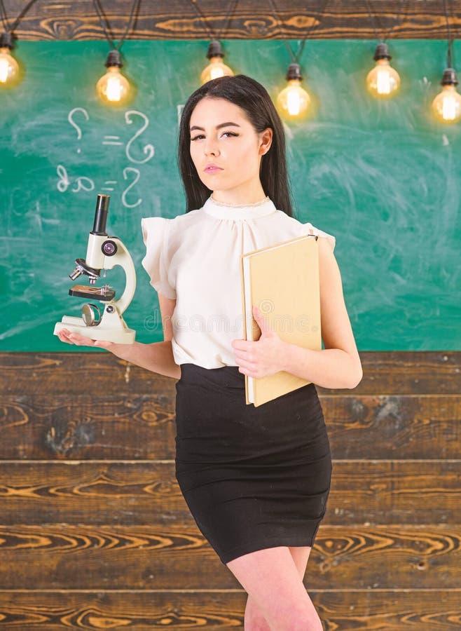 Учитель биологии держит книгу и микроскоп Ученый дамы держит книгу и микроскоп, доску на предпосылке, экземпляре стоковые фото