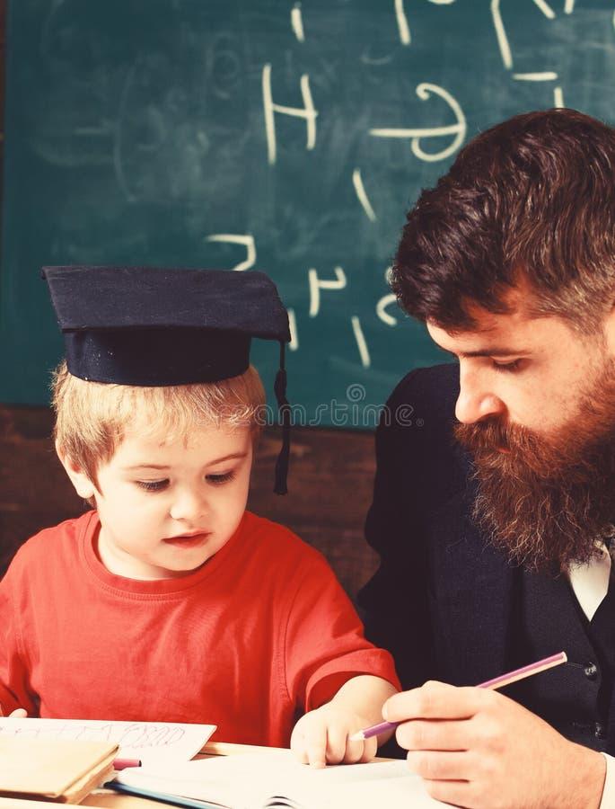 Учитель в официальной носке и зрачке в mortarboard в классе, доске дальше стоковая фотография
