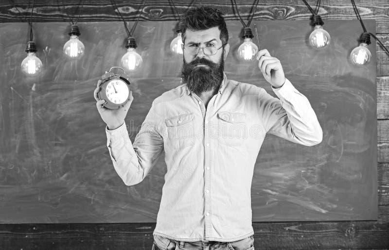 Учитель в eyeglasses держит будильник и ручку Концепция дисциплины Человек с бородой и усик на строгих стойках стороны стоковая фотография