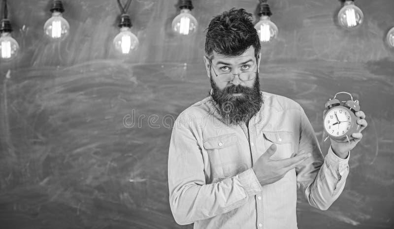 Учитель в eyeglasses держит будильник Концепция дисциплины Человек с бородой и усик на строгой стойке стороны внутри стоковое изображение rf