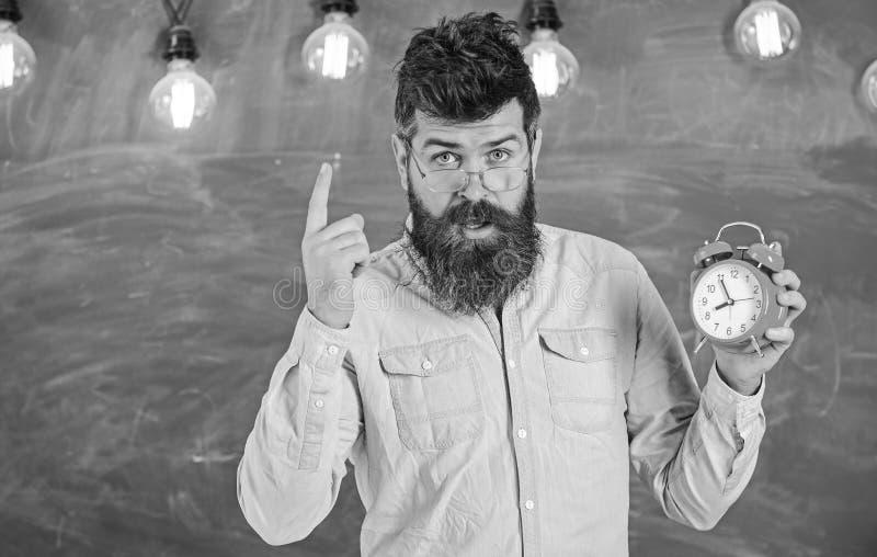 Учитель в eyeglasses держит будильник Концепция дисциплины Человек с бородой и усик на строгой стойке стороны внутри стоковое фото rf