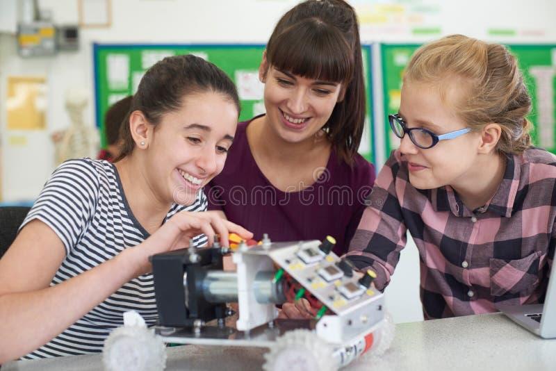Учитель говоря к женским зрачкам изучая робототехнику в науке Le стоковое фото