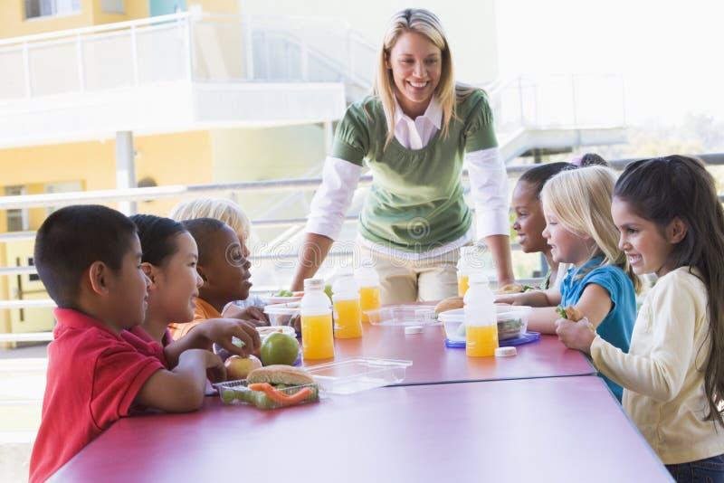 учитель детсада детей наблюдая стоковая фотография
