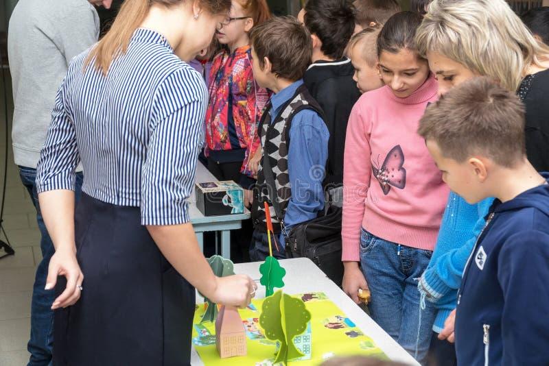 Учитель женщины помогает или показывает что-то к студентам стоковая фотография
