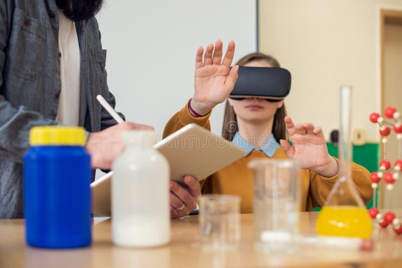 Учитель используя стекла виртуальной реальности и представление 3D для того чтобы научить студентам в классе химии VR, обучение,  стоковое фото rf
