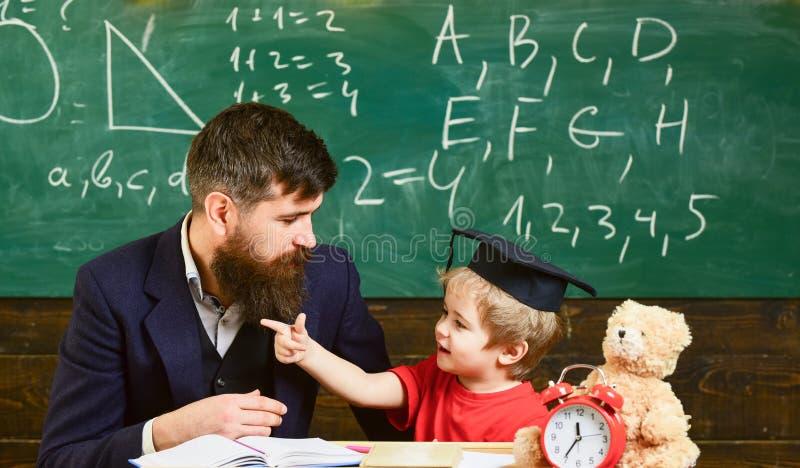 Учитель и зрачок в mortarboard, доске на предпосылке Капризная концепция ребенка Отец с бородой, учитель учит стоковые фотографии rf