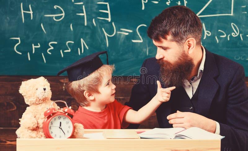 Учитель и зрачок в mortarboard, доске на предпосылке Капризная концепция ребенка Отвлекать ребенк жизнерадостный пока стоковые фото