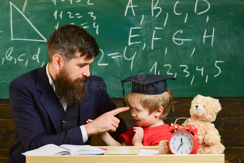 Учитель и зрачок в mortarboard, доске на предпосылке Отвлекать ребенк жизнерадостный пока изучающ, синдром дефицита внимания стоковая фотография rf
