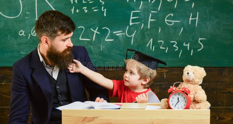 Учитель и зрачок в mortarboard, доске на предпосылке Отвлекать ребенк жизнерадостный пока изучающ, синдром дефицита внимания стоковые фотографии rf