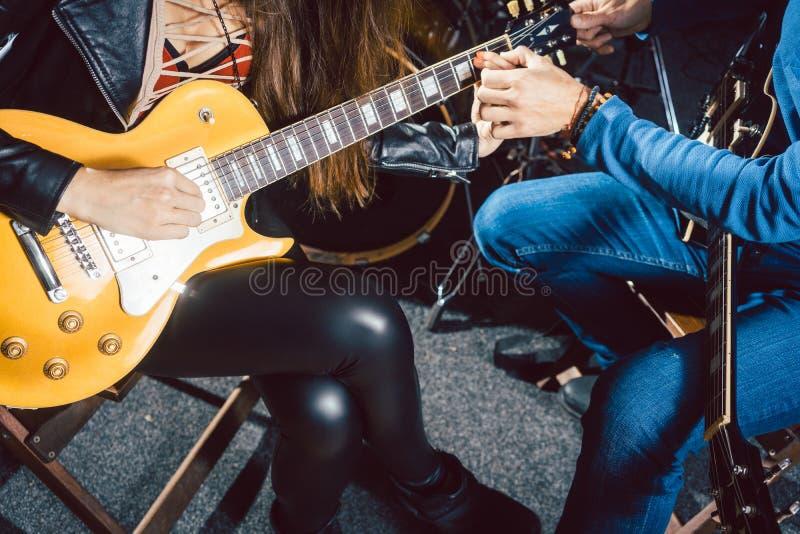 Учитель музыки гитары помогая его студенту стоковые изображения