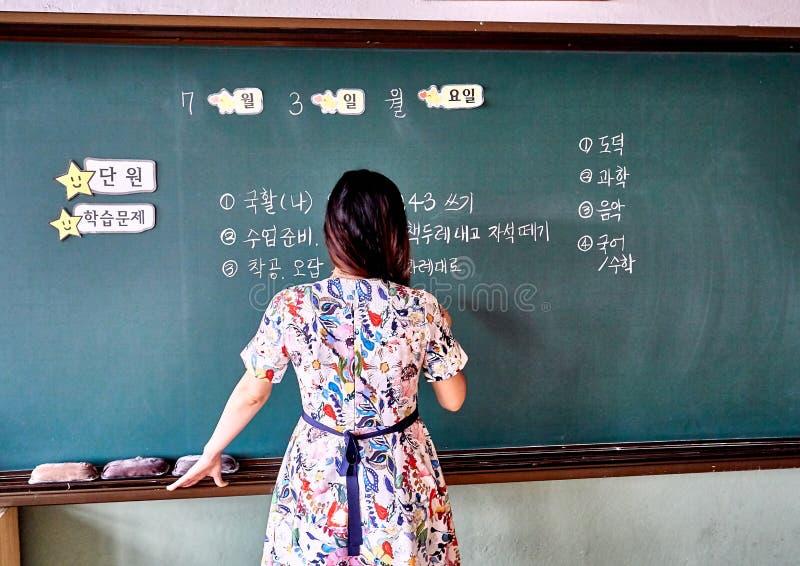 Учитель начальной школы на Южной Корее писать задачи дня на классн классном стоковые изображения rf