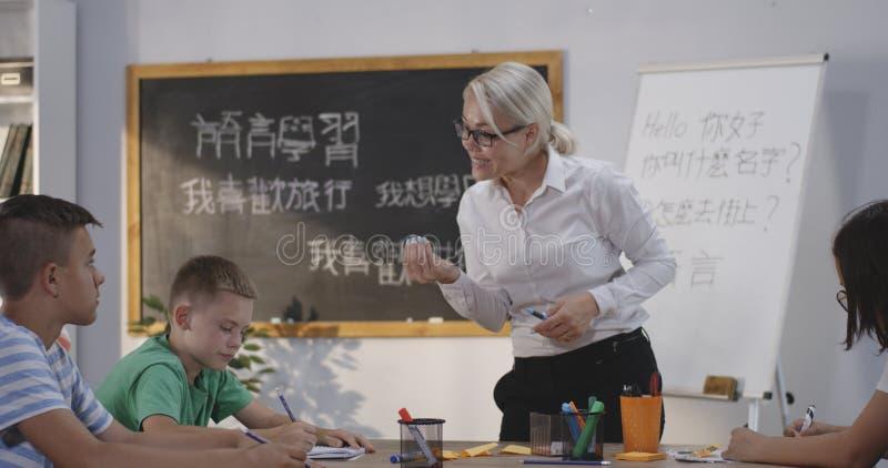 Учитель объясняя зрачкам в классе китайского языка стоковое фото
