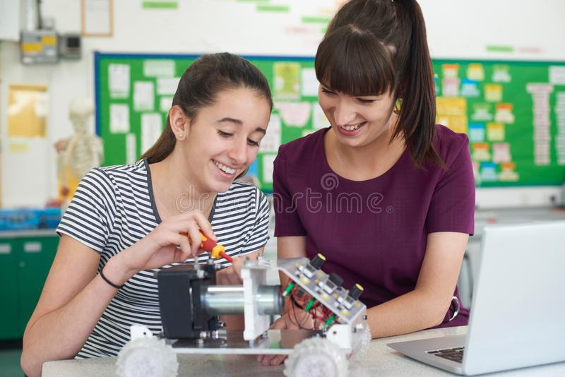 Учитель при женский зрачок изучая робототехнику в уроке науки стоковые фотографии rf