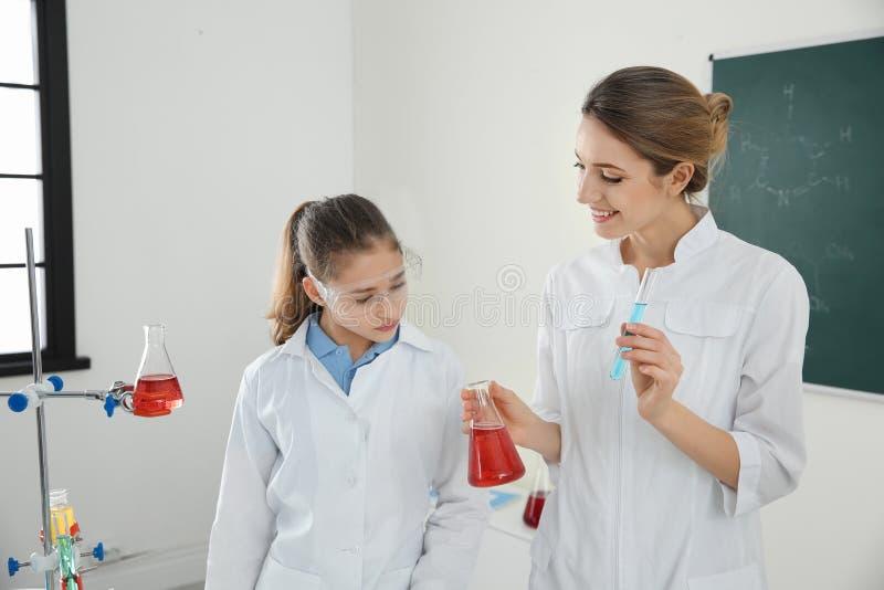 Учитель со зрачком делая эксперимент в классе стоковые фото
