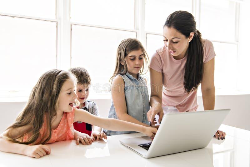 Учитель с группой в составе ребята школьного возраста с ноутбуком на фронте стоковое изображение