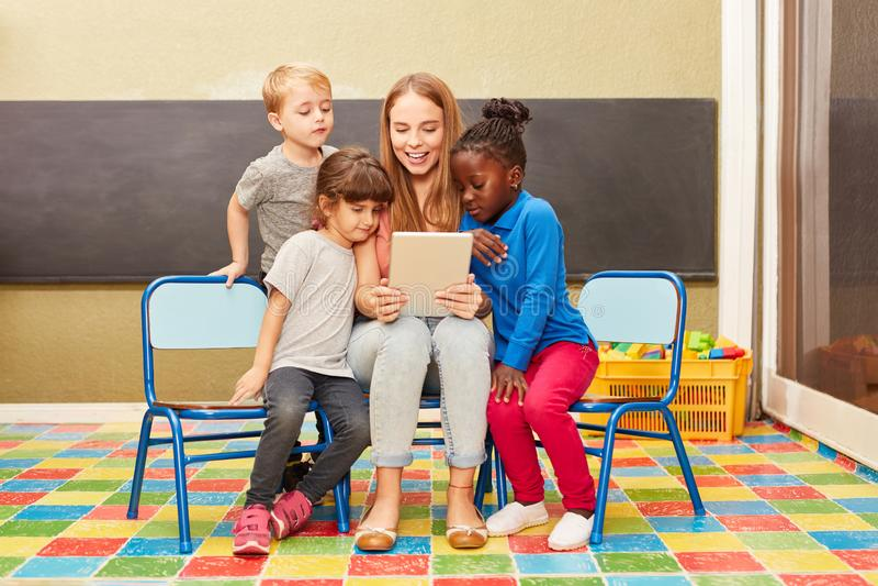Учитель читает от ebook раньше в детском саде стоковая фотография rf