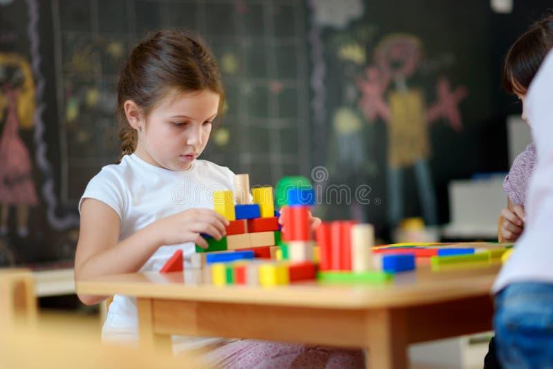 Учитель Preschool при дети играя с красочными деревянными дидактическими игрушками на детском саде стоковые фото