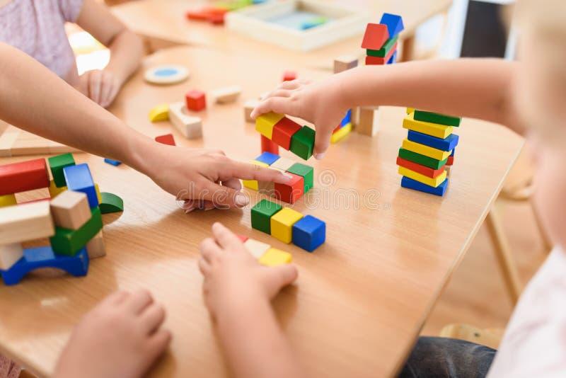 Учитель Preschool при дети играя с красочными деревянными дидактическими игрушками на детском саде стоковые фотографии rf