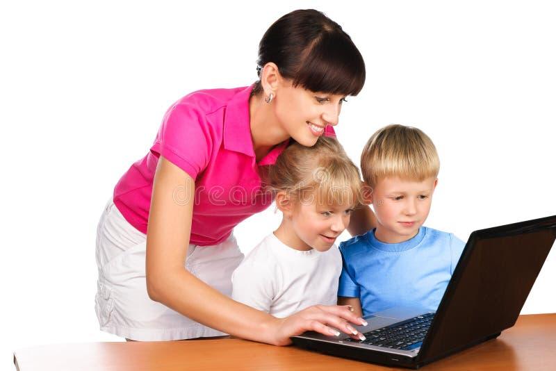 Учитель tutoring элементарные студенты с компьтер-книжкой стоковые фотографии rf