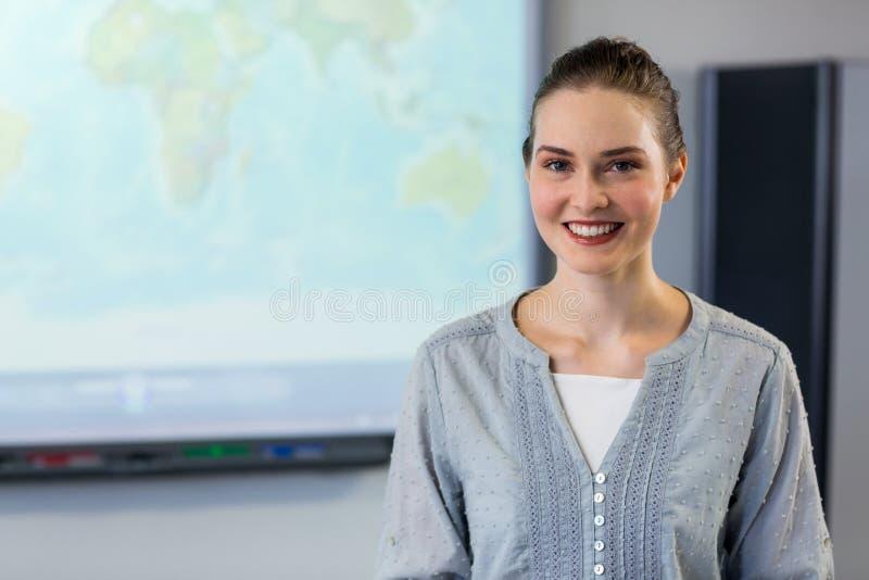 Учительница стоя против экрана репроектора стоковые фото