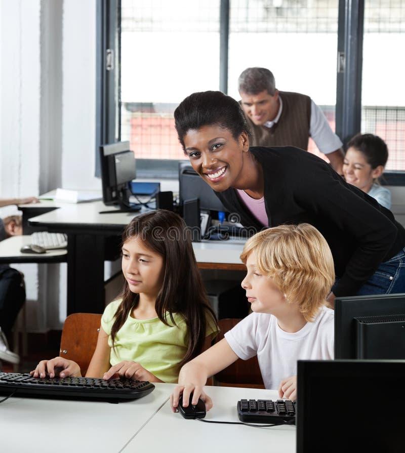Учительница с студентами на столе стоковые изображения rf